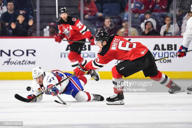 Alexandre Alain of the Laval Rocket dives for the puck against Colton White of the Binghamton Devils during the AHL game at Place Bell on October 12...