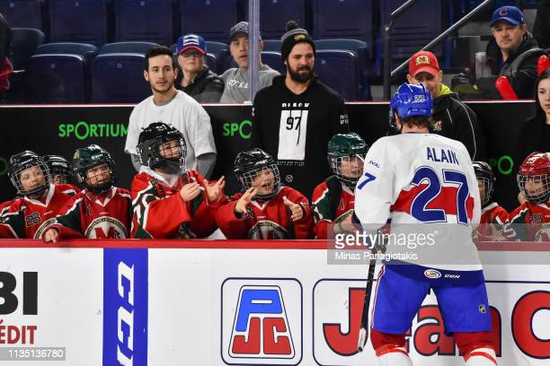 Alexandre Alain of the Laval Rocket hands over pucks to a group of young players on the bench during the warmup prior to the AHL game against the...