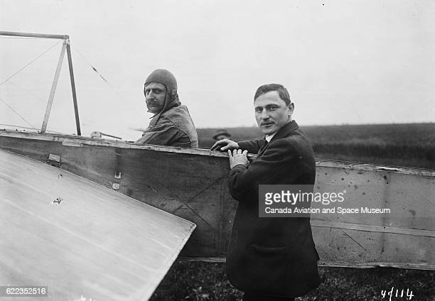 Alexandre Anzani sits in a Bleriot XI monoplane while Louis Bleriot the designer stands nearby