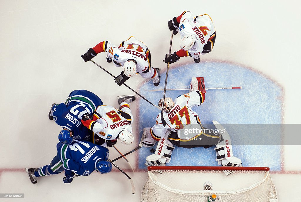 Alexandre Burrows #14 and Daniel Sedin #22 of the Vancouver Canucks try to jam the puck past goalie Joni Ortio #37 of the Calgary Flames while Mark Giordano #5, Mikael Backlund #11 and T.J. Brodie #7 help defend on the play during the second period in NHL action on January 10, 2015 at Rogers Arena in Vancouver, British Columbia, Canada.