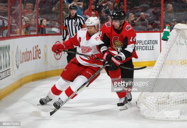 Alexandre Burrows of the Ottawa Senators battles for position against Niklas Kronwall of the Detroit Red Wings behind the net at Canadian Tire Centre...
