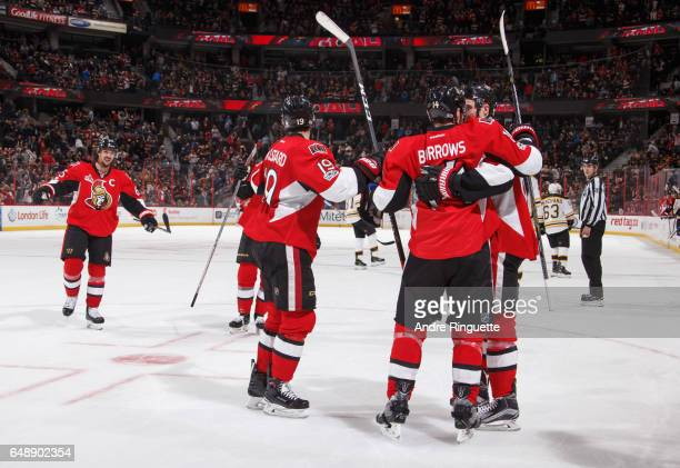 Alexandre Burrows of the Ottawa Senators celebrates his empty net goal against the Boston Bruins with teammates Erik Karlsson Derick Brassard and...