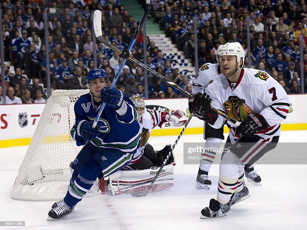 Alexandre Burrows #14 of the Vancouver Canucks and Brent Seabrook #7 of the Chicago Blackhawks try and knock down an airborne puck during the third period in NHL action on February 01, 2013 at Rogers Arena in Vancouver, British Columbia, Canada.
