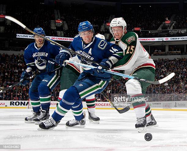 Alexandre Burrows of the Vancouver Canucks and Dany Heatley of the Minnesota Wild battle for the puck during their NHL game at Rogers Arena March 18...