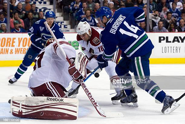 Alexandre Burrows of the Vancouver Canucks battles with Rostislav Klesla of the Phoenix Coyotes for the loose puck after goalie Mike Smith of the...