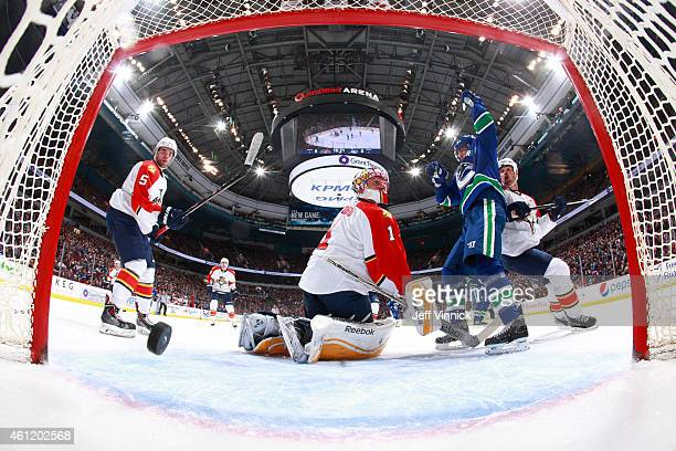 Alexandre Burrows of the Vancouver Canucks celebrates a goal by Daniel Sedin as Willie Mitchell Aaron Ekblad and Roberto Luongo of the Florida...