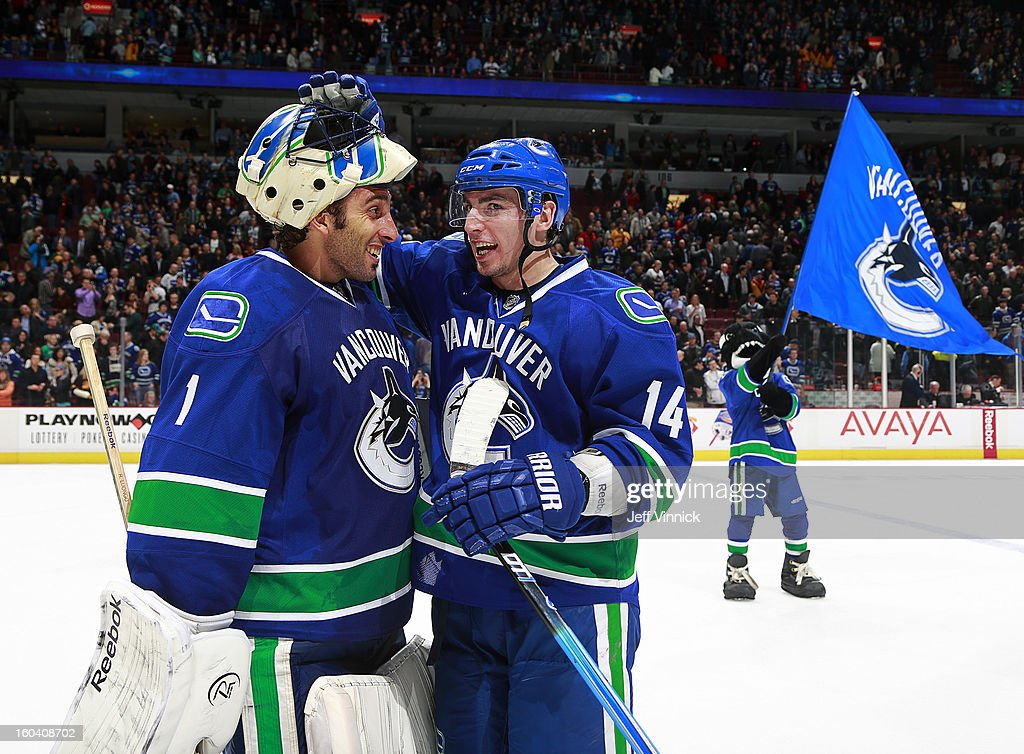 Alexandre Burrows #14 of the Vancouver Canucks congratulates Roberto Luongo #1 after the win over the Colorado Avalanche in their NHL game at Rogers Arena January 30, 2013 in Vancouver, British Columbia, Canada. Vancouver won 3-0.