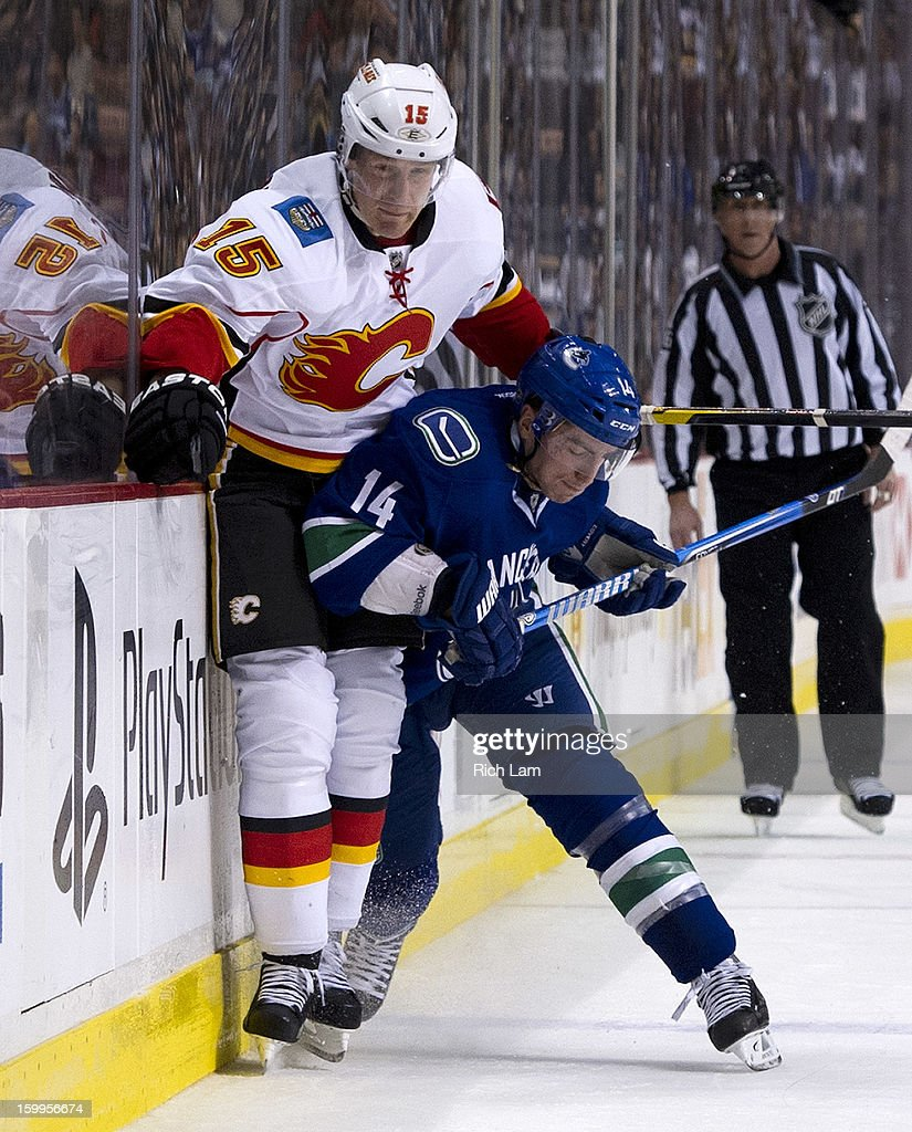 Alexandre Burrows #14 of the Vancouver Canucks hits Tim Jackman #15 of the Calgary Flames along the sideboards during the third period of NHL action on January 23, 2013 at Rogers Arena in Vancouver, British Columbia, Canada.