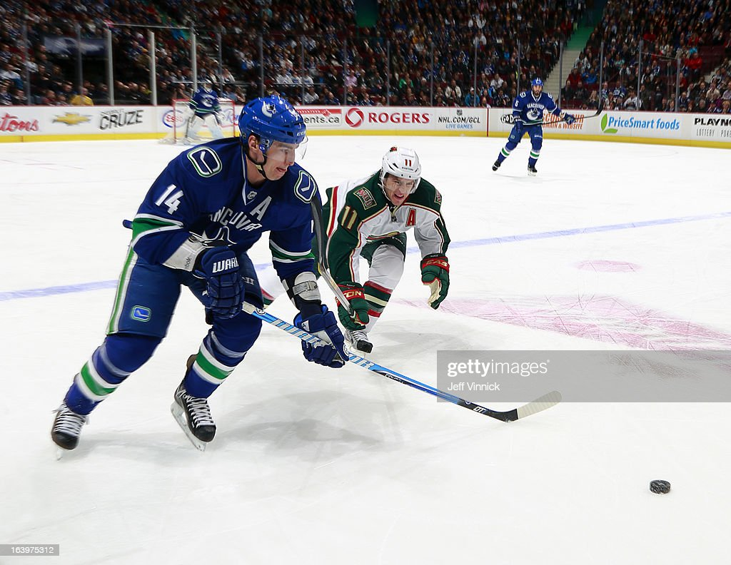 Alexandre Burrows #14 of the Vancouver Canucks out skates Zach Parise #11 of the Minnesota Wild to the puck during their NHL game at Rogers Arena March 18, 2013 in Vancouver, British Columbia, Canada.