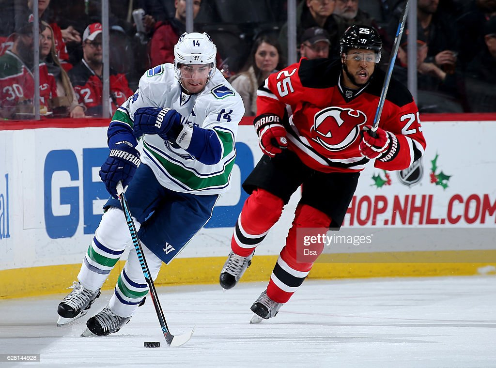 Alexandre Burrows #14 of the Vancouver Canucks takes the puck as Devante Smith-Pelly #25 of the New Jersey Devils defends on December 6, 2016 at Prudential Center in Newark, New Jersey.