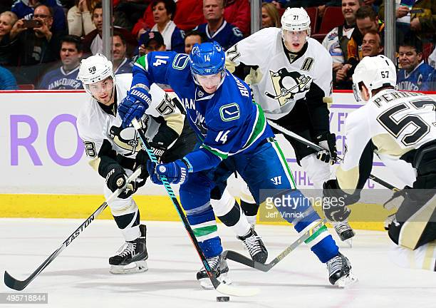 Alexandre Burrows of the Vancouver Canucks works the puck against David Perron Kris Letang and Evgeni Malkin of the Pittsburgh Penguins during their...