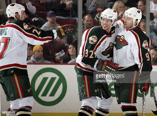 Alexandre Daigle of the Minnesota Wild is congratulated by teammates Marc Chouinard and Kyle Wanvig after his goal in the second period against the...