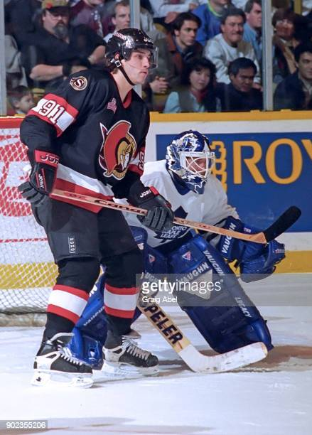 Alexandre Dangle of the Ottawa Senators skates against Damian Rhodes of the Toronto Maple Leafs during NHL game action on December 5, 1995 at Maple...
