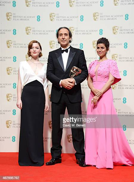 Alexandre Desplat winner of the Original Music award for The Grand Budapest Hotel poses with presenters Holliday Grainger and Nimrat Kaur in the...