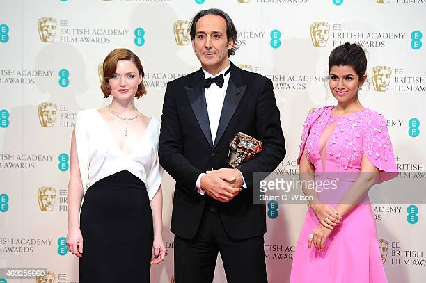 Alexandre Desplat winner of the Original Music award for 'The Grand Budapest Hotel' poses with presenters Holliday Grainger and Nimrat Kaur in the...
