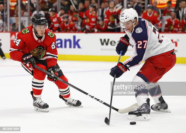 Alexandre Fortin of the Chicago Blackhawks and Ryan Murray of the Columbus Blue Jackets battle for the puck during a preseason game at the United...