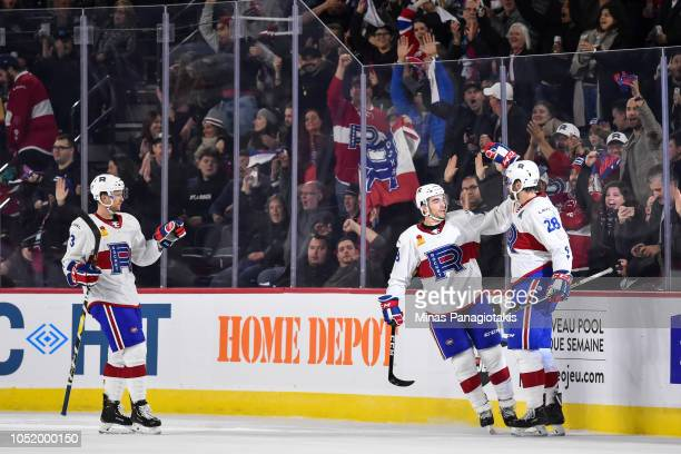 Alexandre Grenier of the Laval Rocket celebrates a first period goal with teammates Kenny Agostino and Brett Kulak against the Binghamton Devils...