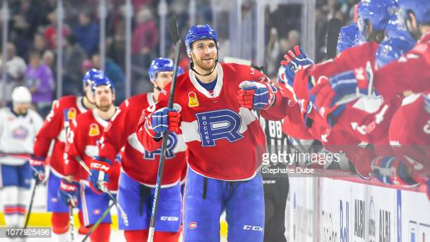 Alexandre Grenier of the Laval Rocket highfives his teammates after scoring his goal against the Rochester Americans at Place Bell on January 5 2019...