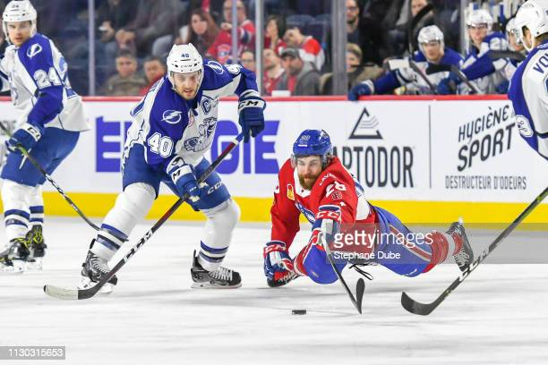 Alexandre Grenier of the Laval Rocket reaches for the puck from Gabriel Dumont of the Syracuse Crunch at Place Bell on March 13 2019 in Laval Quebec