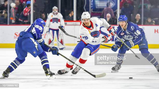 Alexandre Grenier of the Laval Rocket trying to deke Olivier Archambault of the Syracuse Crunch and Otto Somppi of the Syracuse Crunch at Place Bell...
