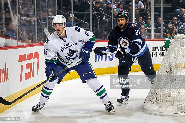 Alexandre Grenier of the Vancouver Canucks and Dustin Byfuglien of the Winnipeg Jets follow the play around the net during first period action at the...