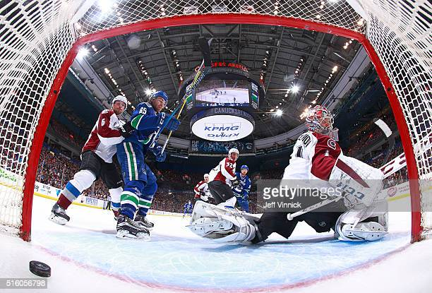 Alexandre Grenier of the Vancouver Canucks and Erik Johnson of the Colorado Avalanche watch as Henrik Sedin of the Canucks scores on Semyon Varlamov...