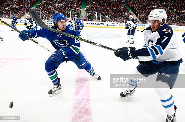 Alexandre Grenier of the Vancouver Canucks checks Ben Chiarot of the Winnipeg Jets during their NHL game against the Vancouver Canucks at Rogers...