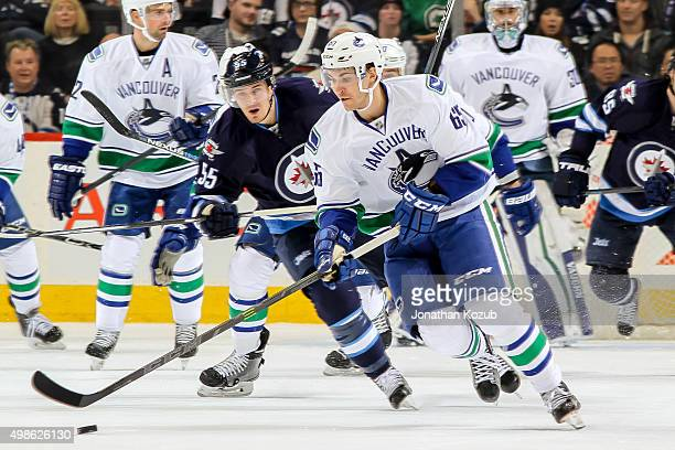 Alexandre Grenier of the Vancouver Canucks plays the puck as Mark Scheifele of the Winnipeg Jets gives chase during first period action at the MTS...