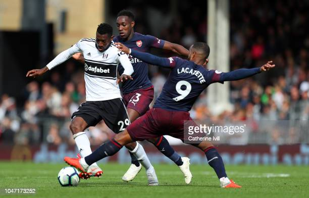 Alexandre Lacazette and Danny Welbeck of Arsenal tackle AndreFrank Zambo Anguissa of Fulham during the Premier League match between Fulham FC and...