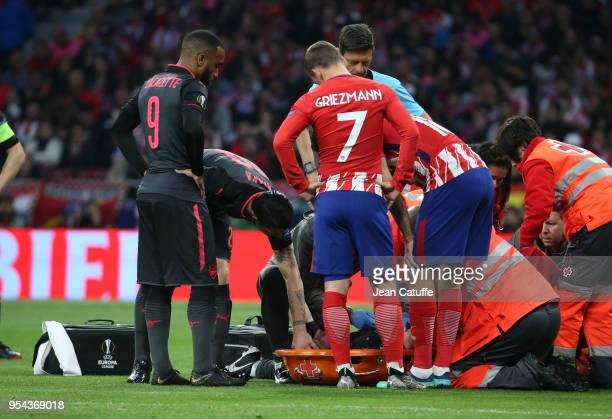 Alexandre Lacazette Granit Xhaka of Arsenal Antoine Griezmann of Atletico Madrid worries for Laurent Koscielny of Arsenal liyng on a stretcher during...