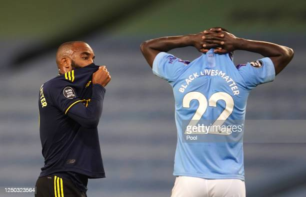 Alexandre Lacazette of Arsenal and Benjamin Mendy of Manchester City react during the Premier League match between Manchester City and Arsenal FC at...
