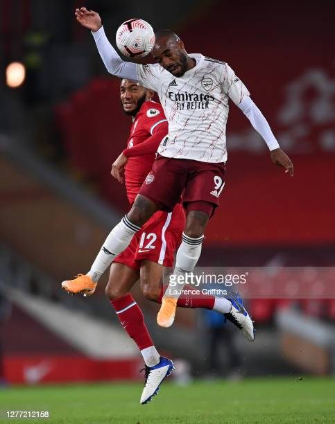 Alexandre Lacazette of Arsenal and Joe Gomez of Liverpool compete for a header during the Premier League match between Liverpool and Arsenal at...