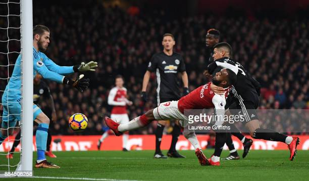 Alexandre Lacazette of Arsenal attempts to shoot as he is challenged by Marcos Rojo of Manchester United during the Premier League match between...