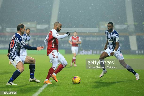Alexandre Lacazette of Arsenal battles with Branislav Ivanovic of West Bromwich Albion and Semi Ajayi of West Bromwich Albion during the Premier...