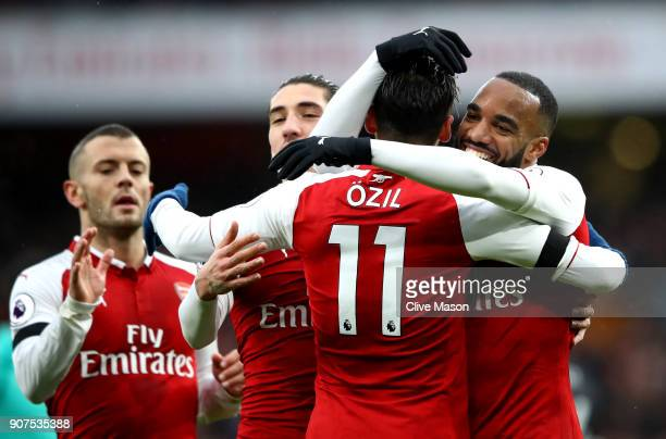 Alexandre Lacazette of Arsenal celebrates scoring his side's fourth goal with Mesut Ozil and team mates during the Premier League match between...