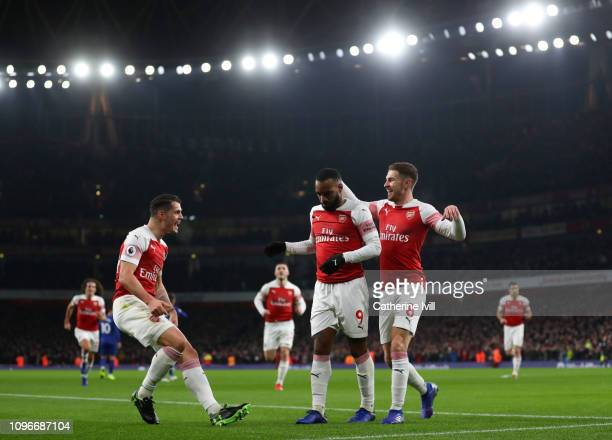 Alexandre Lacazette of Arsenal celebrates scoring his teams first goal with Granit Xhaka and Aaron Ramsey during the Premier League match between...