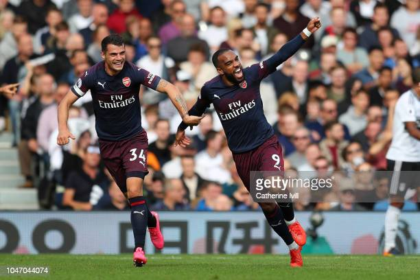 Alexandre Lacazette of Arsenal celebrates with teammate Granit Xhaka after scoring his team's first goal during the Premier League match between...