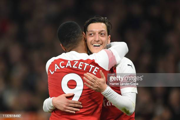 Alexandre Lacazette of Arsenal celebrates with teammate Mesut Ozil after scoring his team's fifth goal during the Premier League match between...