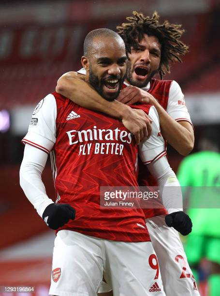 Alexandre Lacazette of Arsenal celebrates with teammate Mohamed Elneny after scoring his team's first goal during the Premier League match between...