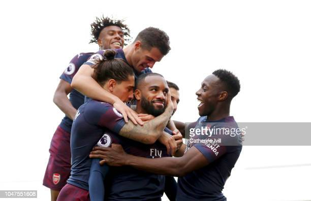 Alexandre Lacazette of Arsenal celebrates with teammates after scoring his team's second goal during the Premier League match between Fulham FC and...