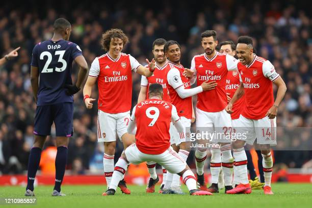 Alexandre Lacazette of Arsenal celebrates with teammates after scoring his team's first goal which was given by VAR during the Premier League match...