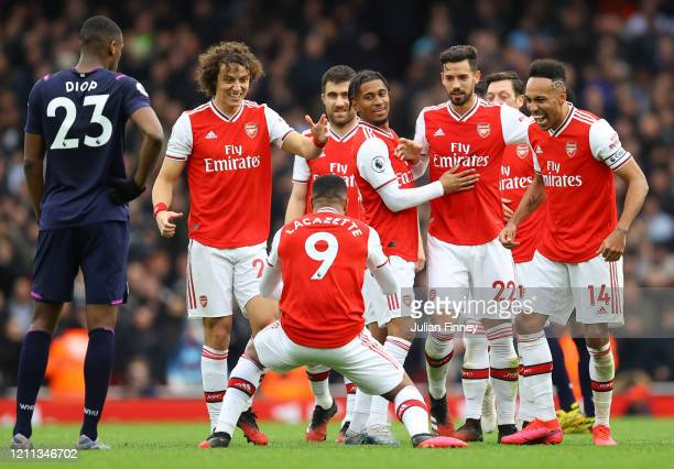Alexandre Lacazette of Arsenal celebrates with teammates after scoring his team's first goal which was awarded after a VAR review during the Premier...