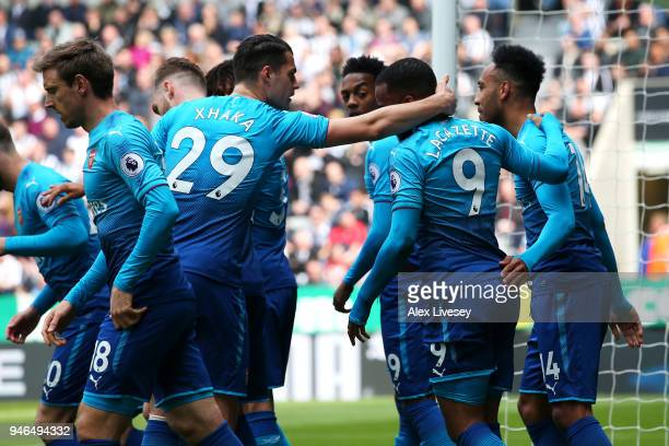 Alexandre Lacazette of Arsenal celebrates with teammates after scoring his sides first goal during the Premier League match between Newcastle United...