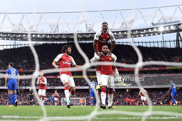 Alexandre Lacazette of Arsenal celebrates with teammates Mohamed Elneny and Danny Welbeck after scoring the opening goal during the Premier League...