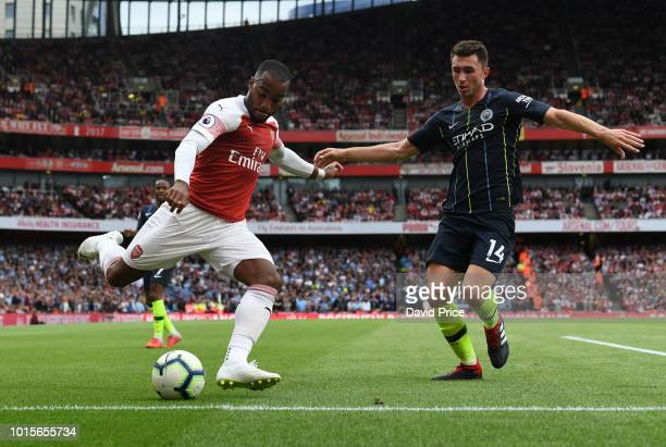 Alexandre Lacazette of Arsenal crosses under pressure from Aymeric Laporte of Man City during the match the Premier League match between Arsenal FC...