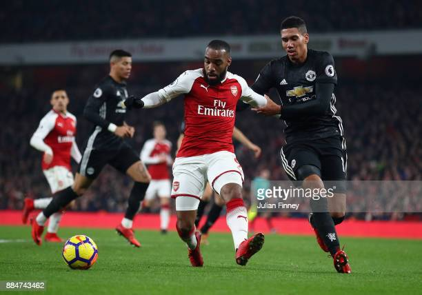 Alexandre Lacazette of Arsenal holds off Chris Smalling of Manchester United during the Premier League match between Arsenal and Manchester United at...