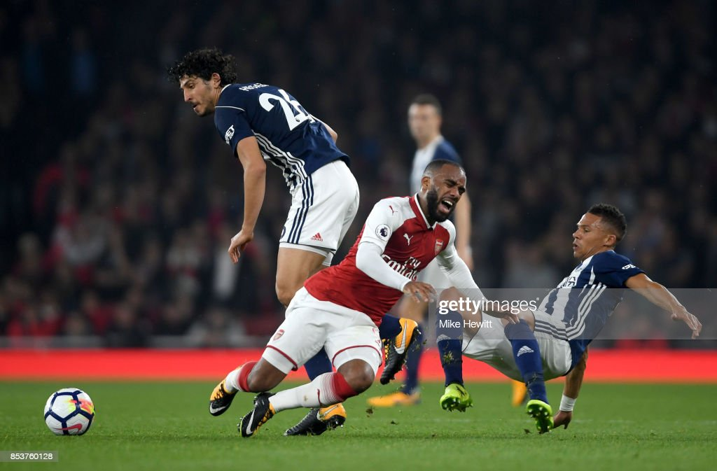 Alexandre Lacazette of Arsenal is challenged by Ahmed El-Sayed Hegazi and Kieran Gibbs of West Bromwich Albion during the Premier League match between Arsenal and West Bromwich Albion at Emirates Stadium on September 25, 2017 in London, England.