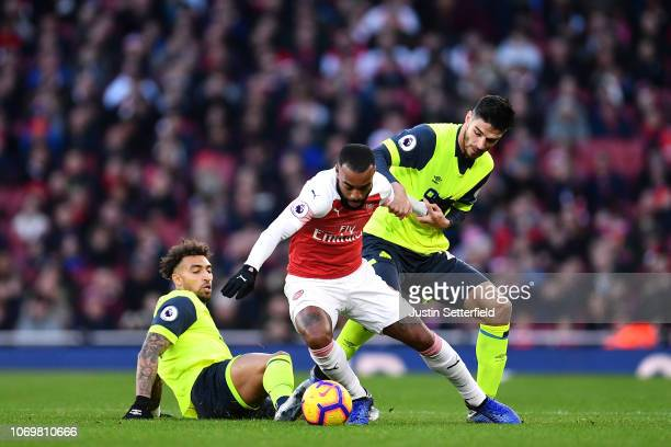 Alexandre Lacazette of Arsenal is challenged by Daniel Williams of Huddersfield Town and Christopher Schindler of Huddersfield Town during the...