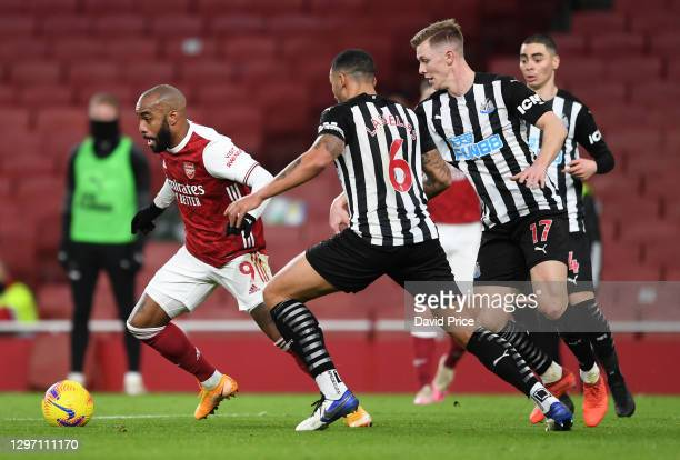 Alexandre Lacazette of Arsenal is challenged by Jamaal Lascelles and Emil Krafth of Newcastle during the Premier League match between Arsenal and...