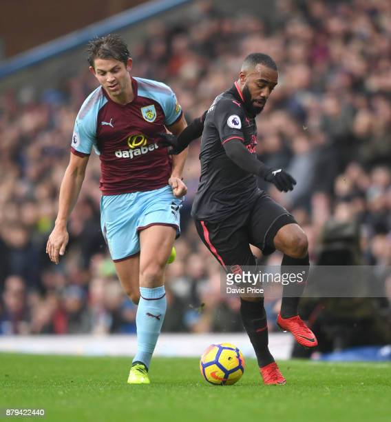 Alexandre Lacazette of Arsenal is challenged by James Tarkowski of Burnley during the Premier League match between Burnley and Arsenal at Turf Moor...